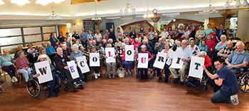 """Grey Gables Residents Holding \""""We Color It\"""" Letters"""