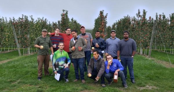 Hackathon competitors at T and K Ferri Orchards, eating apples and posing in front of rows of apple trees