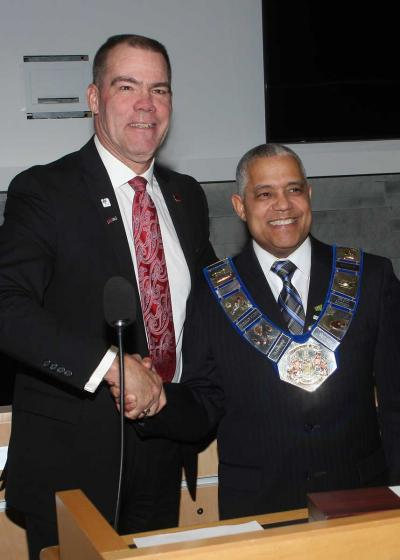 "Brian Milne, past warden and current Grey County Councillor, presents Selwyn ""Buck"" Hicks with the Chain of office."
