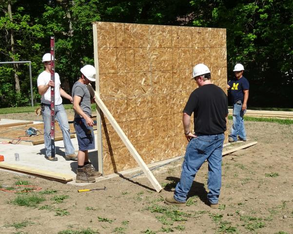 A group of volunteers work together to raise the first wall on pavilion.