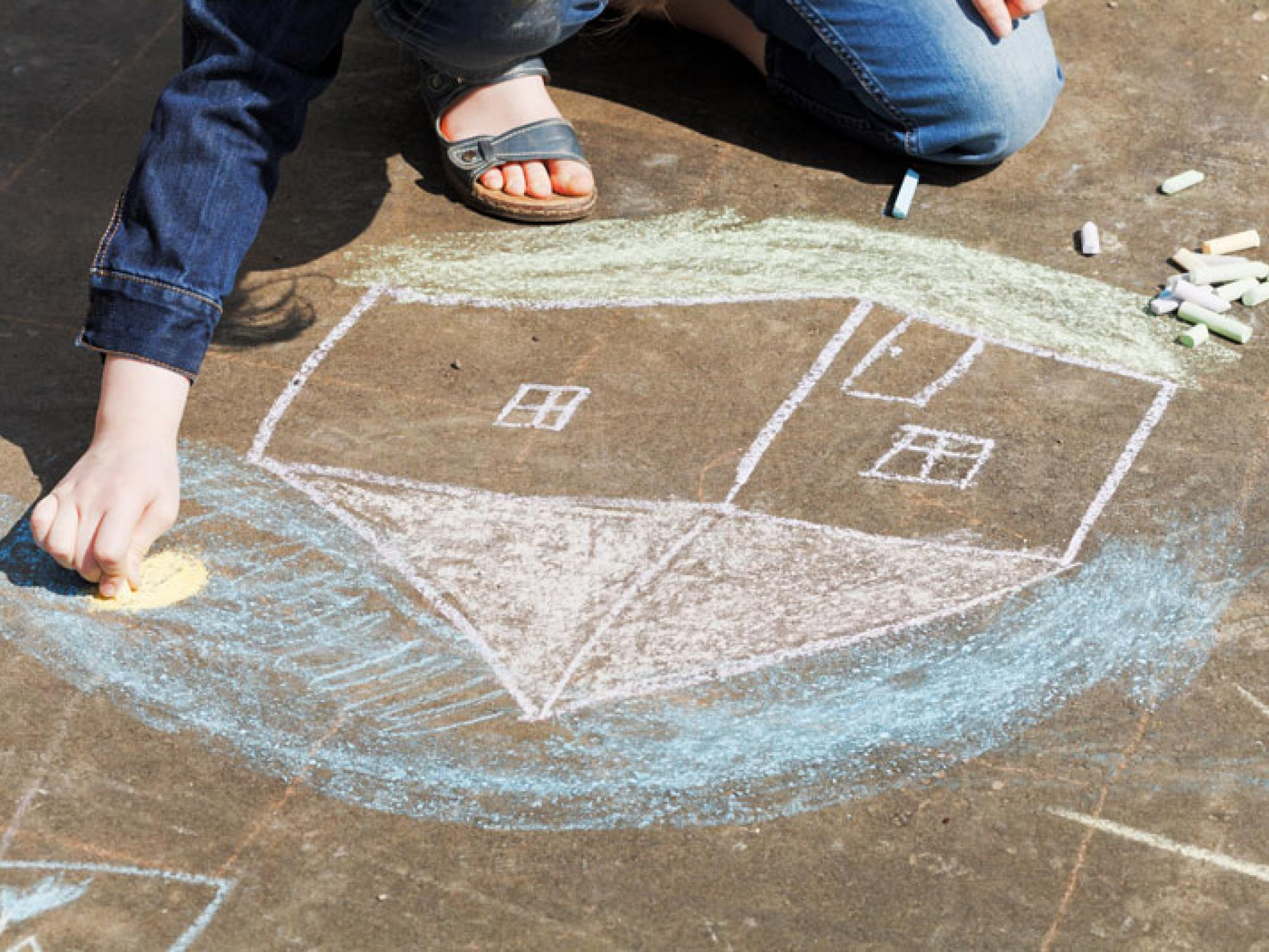 A child uses chalk to draw a house on the ground