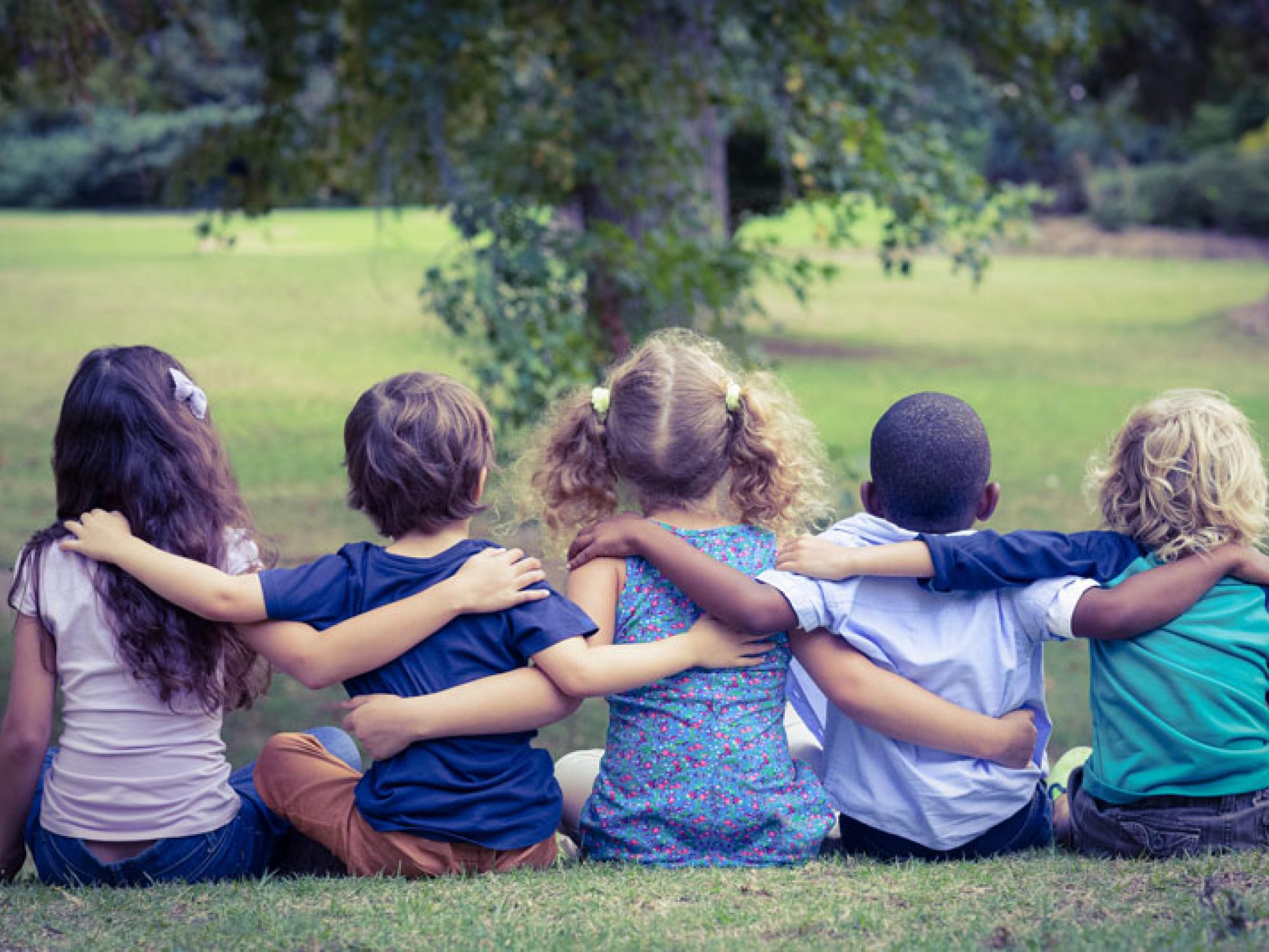 Five children sit arm in arm in the park.