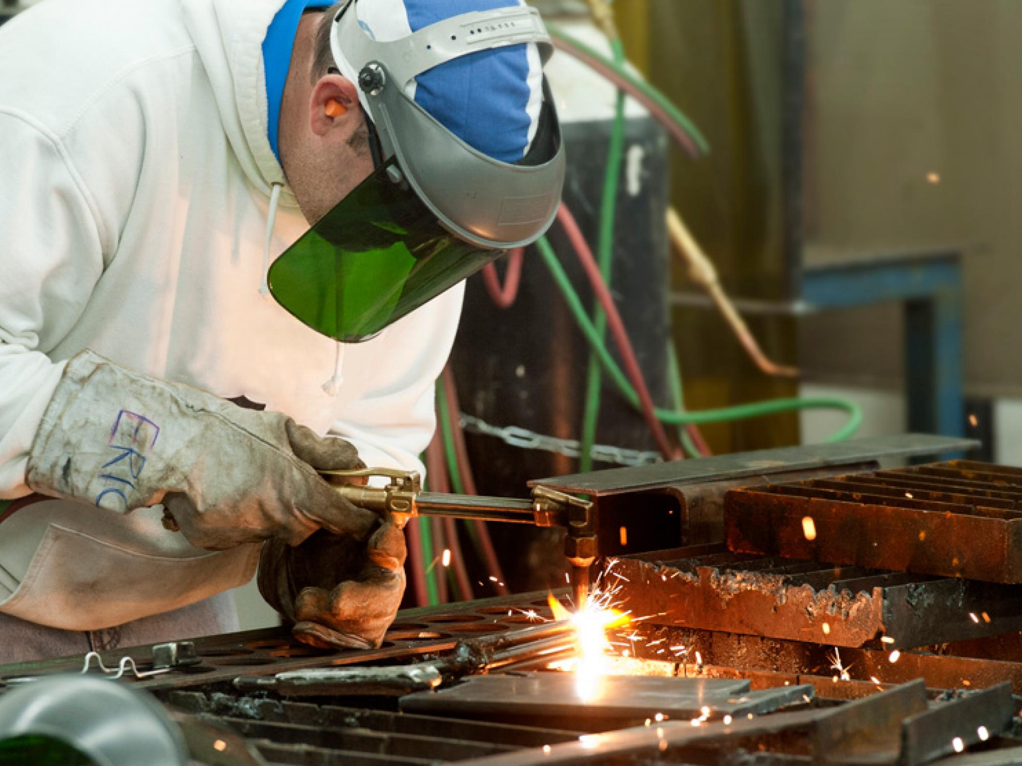 Sparks fly as a man with a welding torch works on a piece of metal.