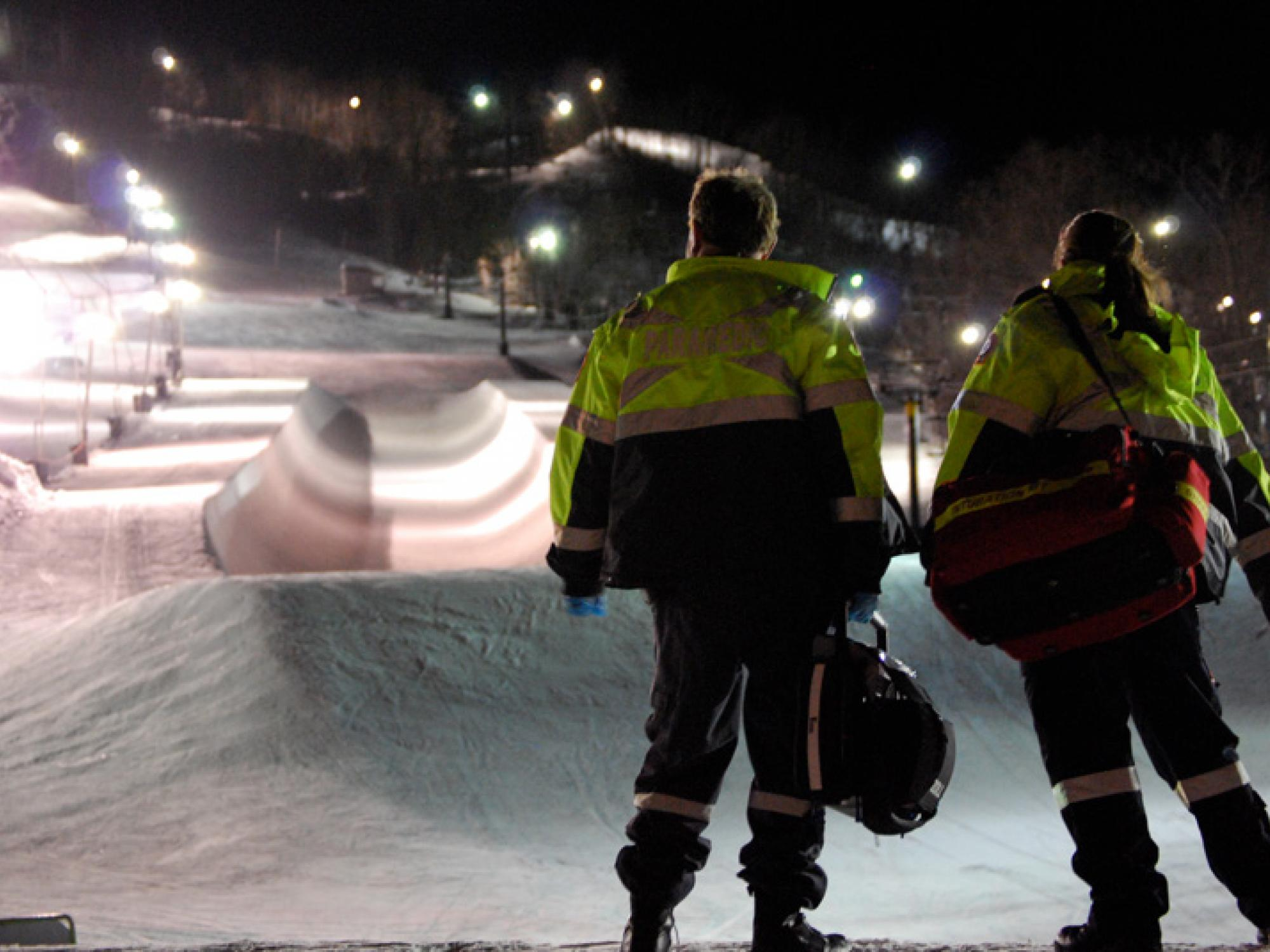 Two paramedics stand at the base of blue mountain as it is lit up at night.