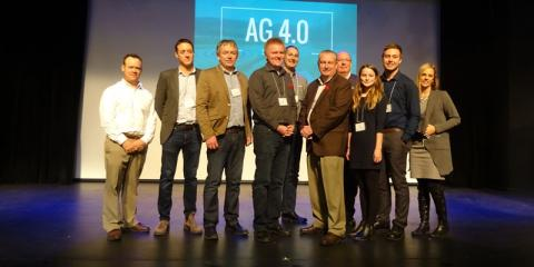 A group of people stand on the stage in front of the banner for Ag 4.0
