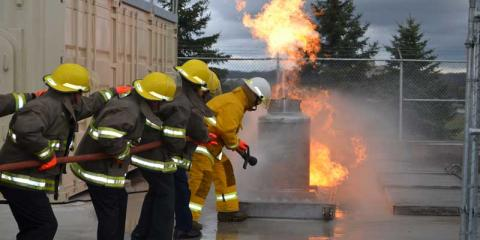 People in firefighting gear battle a flame at the marine emergency duties training facility.