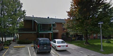 Two storey brick building surrounded by trees