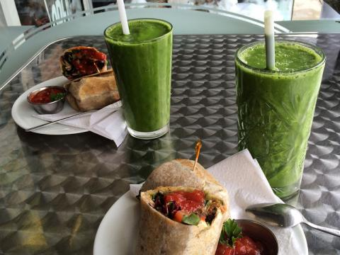 Two smoothies and two wraps are displayed on a table