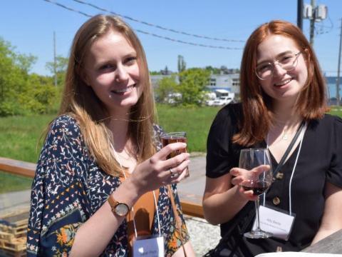 Two young women  sit on the Thornbury Cider patio,