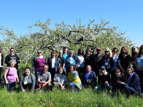 Fam Tour group poses in front of an apple orchard.