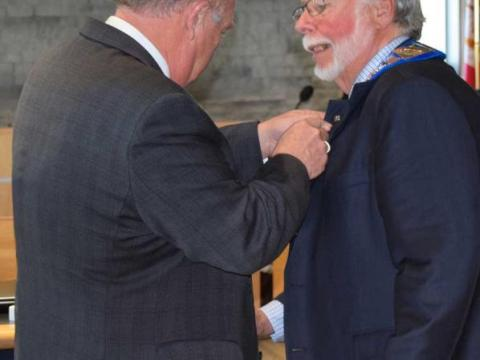 Alan Barfoot applies a pin to the collar of Warden Halliday's suit jacket.