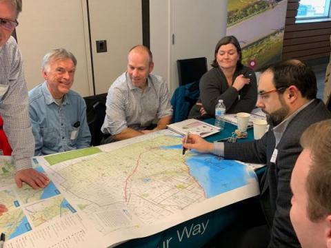 workshop participants have a discussion around a cycling map