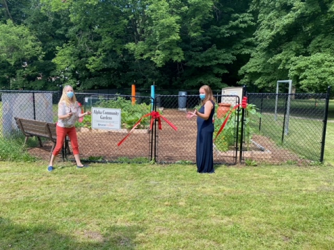 Anne Marie Shaw (left) and Maggie Tieman (right) cutting ribbon together at Alpha Street Community Garden