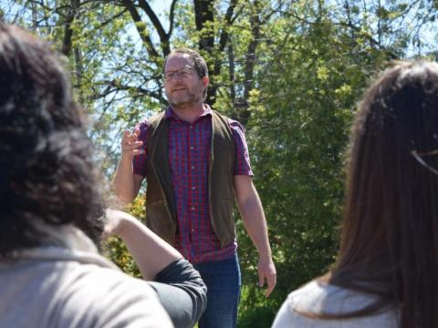 Picture of a man standing outside in the sun explaining to a group of people what Rocky Shores Health and Wellness does