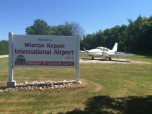Sign reading Wiarton Keppel International Airport. There is a small airplane behind the sign with two props.