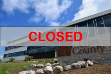 Grey County building with large text saying CLOSED