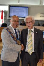 Warden Selwyn Hicks shakes hands with newly sworn in alternate councillor Ross Kentner.