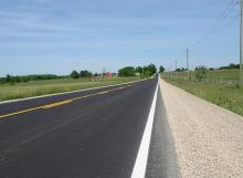A freshly resurfaced Grey County road runs runs into the horizon. There is a farm with a large red barn in the distance.  Both sides of the roads are lined with hay fields.