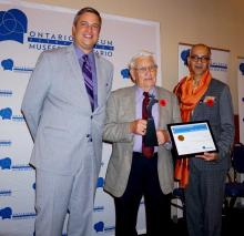 Gilbert Rice receives a framed certificate to recognize his OMA Volunteer Award