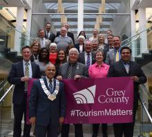 Members of council and Tourism staff hold the Tourism Week Banner on the steps in the Admin. Building