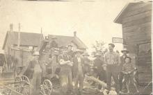 Black and white photograph with a group of people standing in the centre of a small village.  The picture looks to be quite old.