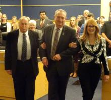Alan Barfoot is lead to the Warden's chair by fellow County Councillors Gail Ardiel and Harley Greenfield