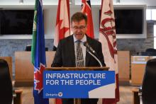 MPP Walker at the podium announcing infrastructure funding.