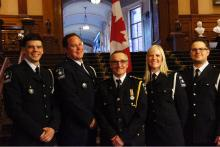 Five Grey County paramedics wearing their formal uniforms stand in front of a Canadian flag inside queen's park in Toronto.