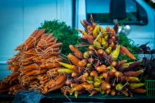 Bundles of fresh root vegetables are tied together and displayed on a table at a local farmers' market