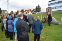 Councillors and staff gather on the lawn in front of the Administration Building as a wreath is laid at the war memorial.