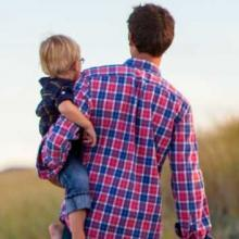 Photo of a father in a plaid shirt carrying a young, blonde haired toddler through a field.