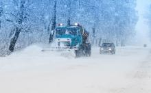 A snow plow pushes snow off the road
