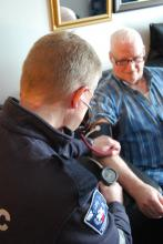A community paramedic leans over an elderly man and checks his blood pressure.